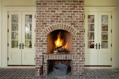 Shape of fireplace and place for wood + nice antique brick; French doors