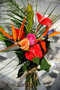 A tropical bouquet of roses and birds of paradise