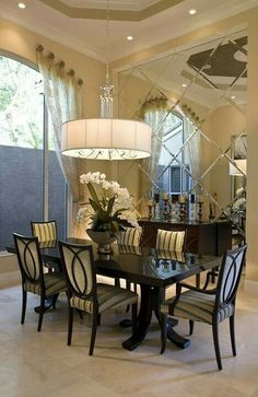 Beautiful light yellow room with yellow and dark striped chairs.   Dark wood table plus a wonderful chandelier that is all reflected in the diamond shaped mirrors on one wall.