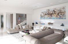 salon spacieux blanc avec deux canapés en beige, tableau abstrait en bleu et beige et niche de rangement blanche