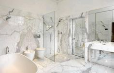 Master of Marble. A sleek glass shower and a freestanding tub are surrounded by expansive slabs of marble in the master bathroom.