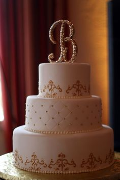 Intricate gold piping, quilting, gold pearls, and a sparkling monogram make this wedding cake a showstopper.