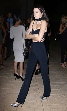 Kendall Jenner wears a high-neck crop top, high-waisted pants, shoulder bag, and silver pumps