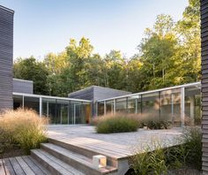 Located on a land conservancy, a collection of wood-clad cubes orient toward a pond on a sloped site. These eight forms touch the ground lightly and follow the contours of the land, linked by glass enclosed hallways. The simple shapes are strong silhouettes in an agricultural landscape, organized in a shifting grid akin to farming plots in the area. Inspired by writer and artist residency retreats, the house configuration allows for introspection and cloistered bedroom suites, in…