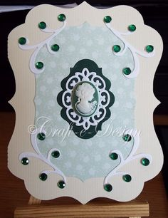 Enjoyed making this little card. The basic card I cut with my cameo machine, next I cut the topper layers (patterned, green and white) with Spellbinders dies. The white corner flourishes are cut using Sue Wilson dies. I attached all of these with Tattered Lace detail glue. I love this glue as it dries quickly and clearly. I had the cameo in my stash and added that with the same glue. I finished off with emerald green gems on the corner flourishes. It has a blank insert. £1.50 + £1.00 p&p.