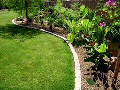 Tropical landscape installation using brick header between grass and landscaping in Scottsdale, AZ. - www.lonestaraz.com