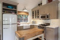 Country Kitchen with Complex marble counters, Inset cabinets, Big Chill Original Size Retro Fridge in White!