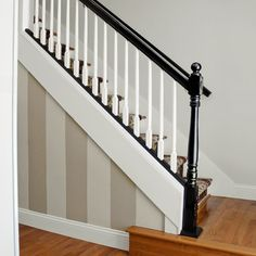 A now-open staircase lined with a handsome new balustrade and highlighted by surrounding warm beige paint and a floral runner makes it an entryway showpiece.