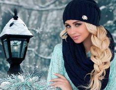 Девушка в вязаной шапке и шарфе на фоне падающего снега