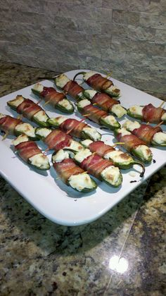 Jalapeno Poppers  Slice jalapeno peppers in half lengthwise.  Remove seeds. Fill with cream cheese. Wrap with half-slice of bacon (we use Boar's Head) and secure with toothpick. Bake at 425. Recipe says 12 minutes.  I baked at 17 minutes for crispy bacon.