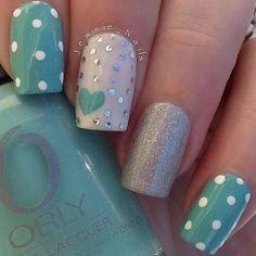 Estilosas uñas en azul turquesa decoradas con lunares blancos, en color beige con hexágonos plateados y un corazón, y otra decoradas con brillos color plata.