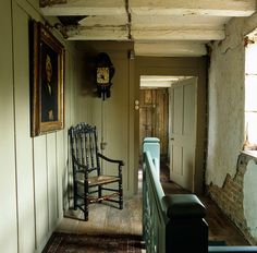 Newly painted wood panelling contrasts with the original crumbling brick and plaster walls on this landing ~ Arne Maynard in Lincolnshire, UK.