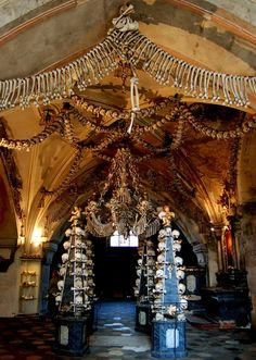 """The 40,000 skeletons within Sedlec Ossuary (aka Kostnice Ossuary Beinhaus) in the Czech Republic welcome you, quite literally, with open arms. Known to most as """"The Bone Church,"""" it displays some of the world's more macabre art. In addition to a splendid bone chandelier composed from almost every bone in a human body, the ossuary displays two large bone chalices, four baroque bone candelabras, six enormous bone pyramids, two bone monstrances (a vessel used to display the Eucharistic host)"""
