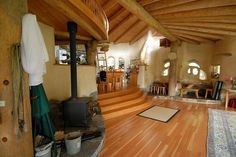 Cob House interior ... I love the rustic, cave-like quality of cob homes ... love the hardwood here