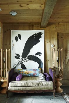 Antique daybed covered in bolsters and throw pillows beneath abstract art.