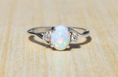 This stunning white lab opal has amazing flashes of color, it compliments a large variety of accent colors. The white opal is hand set, along with cubic zirconia accent stones, into an elegant sterling silver setting. Select your choice of side accent stones to create a unique custom ring... These rings are true to size, each ring is sized by hand and double checked before shipment. Setting Material - Stamped 925 Sterling Silver Center Gemstone- Gemstone: Opal Type: Lab Created Color…