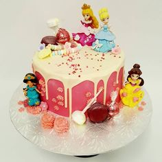 Smooth bright pink cake with drip and Disney Princess Figurines