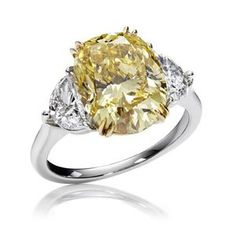 Classic Winston Ring in platinum, with an oval yellow diamond center stone and half moon white diamond side stones.