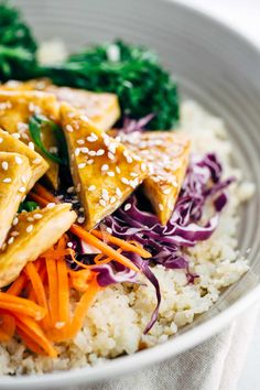 Pieces of teriyaki tofu in a bowl with cauliflower rice and vegetables