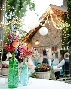 Bright flowers and glass vases compliment the surrounding flowers and hanging string lights. Bright Flowers, Red Flowers, Verbena, Amazing Weddings, Real Weddings, Colored Glass Vases, Red Wedding Flowers, Outside Wedding, Wedding Photos