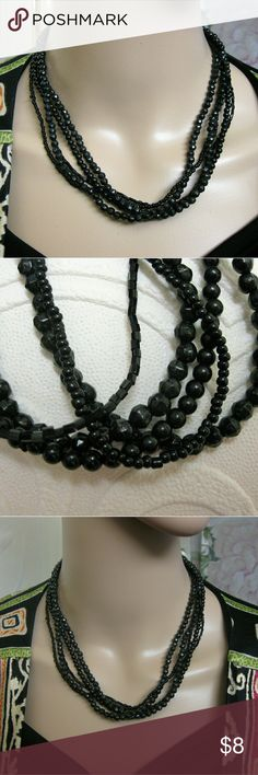 """Black Glass Bead Multi-Strand Silver Necklace Charming black glass bead multi-strand necklace that may be worn for any occasion.  This contemporary piece features five (5) strands of circular, tube and faceted beads.  These pick up the light for subtle sparkling  glints.      Silver tone ends and chain with a secure lobster clasp.      17.4g   Bead dimensions 1/8"""" - 1/16""""  (717AO119) Jewelry Necklaces"""