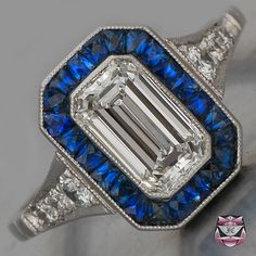Deco engagement ring, diamond surrounded by really excellent sapphires, in platinum setting. I really would rather see this in a warm gold setting. Blue looks best next to gold - Go Bears!!
