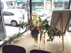Back side of the big flower arrangement in the art gallery window #mdisplay 💞 roses, hanging amaranthus, poke berry, eucalyptus, apple