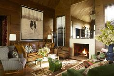 Designer John Oetgen used classic furnishings and large-scale art to enliven the rustic, oak-paneled North Carolina living room. Antique Knole sofa; vintage Parsons table; vintage Billy Baldwin slipper chair; frog stool, Bergdorf Goodman; rugs, Moattar and Stark; photograph, Hugh Hales-Tooke. Read about how John Oetgen infused his home with rustic appeal here.