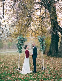 This fall inspired wedding was framed perfectly by orange leaves and this handcrafted birch tree backdrop.