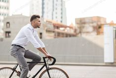 man with headphones riding bicycle on city street photo by dolgachov on Envato Elements
