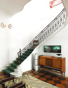 White and black staircase with green carpeting