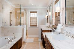 This bathroom offers both functionality and style. A creamy Calcutta marble backsplash behind the shower pairs beautifully with the warm wood vanity and bathtub surround. Burlap Roman shades offer privacy while allowing light to trickle in through the rustic window treatment.