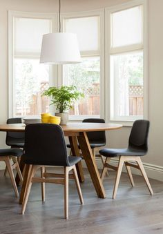 Mid Century Modern dining nook with round table, and drum pendant light.