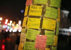 Messages are seen on a 'tree of freedom' as people light candles to commemorate the victims... at Charly Hebdo in Paris.