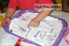 writing letters in a flour tray