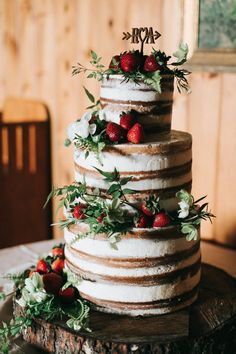 Gorgeous naked wedding cake with strawberries + an adorable topper | Image by Emily Delamater Photography