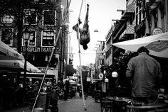 A street performer dressed simply in only a thong, dangles upside down in the Leidseplein square in Amsterdam, June 21, 2009. Leidseplein is one of Amsterdam's most popular centers for nightlife.