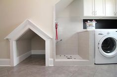 Laundry rooms are ideal for locating a dedicated shower for grooming. This setup lets him dry off in a custom alcove (though we recommend adding a soft bed). Read our essentials for planning a dog cleaning station here.