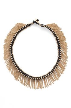 Obsessed with with this edgy choker necklace made with scores of metallic chains and luminous beads.