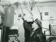 U.S. Navy Airship Squadron 24 crew member inspecting cables, written below the image, 'Checking Cable Tension, Last-minute inspection of all-important controls'; from the booklet, 'An Operational Flight ZP-24'...Credit: unknown (Smithsonian Institution)