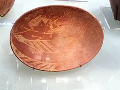 A plate created during the Early Dynastic period of Ancient Egypt. It depicts a man on a boat alongside a Hippopotamus and a Crocodile