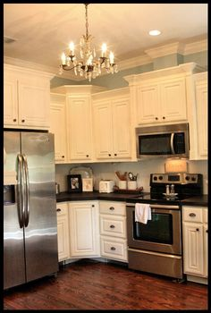 white cabinets and dark floors, stainless, and chandelier