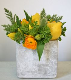 modern arrangement of yellow ranunculus, yellow tulip and lemon with geranium and grass accent in concrete vase