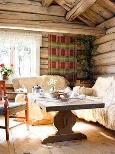 MED UTSIKT TIL PEISEN: Fra stuekroken ser de inn i flammene på peisen og inn til kjøkkendelen. Stolen er gammel, og bordet av nyere dato. Åklene var sydd fast på saueskinnsfellene. Kanskje er de laget på vevstolene som står på gården. Gløden fra tømmeret blir særlig vakker når sollyset finner veien inn i stuen. Scandinavian Cabin, Bedford House, Dining Table, Scandinavian Home, Living Room, Table, Interior, Rustic Dining Table, Home Decor