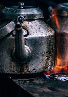 a metal teapot over a gas burner