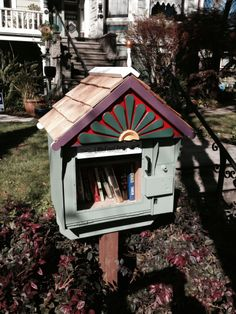 Ken Carvalho. Alameda, CA.  	 Our Little Free Library is made from a recycled Newspaper dispenser we acquired, it has a shelf for paperbacks to sit flat above hardback books lined below. The shape of it and its details match our 1889 Queen Anne Victorian.