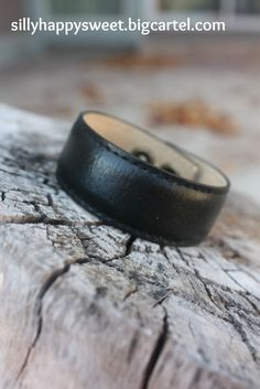 "This black leather cuff measures just short of 1"". It's ready for you to design by using your own personalized words! We'll attach a hand stamped message on a metal blank. Shop open for holiday season."