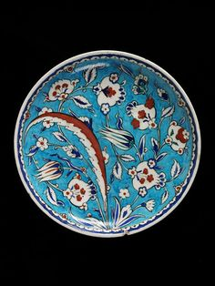 Dish | Iznik, Turkey, 1585-1600 | Dish of whitish-grey fritware, painted in colours and covered with a clear glaze. Circular without rim | Dish of whitish-grey fritware, painted in colours and covered with a clear glaze. Circular without rim | Edge encircled with with a narrow border of cresting | VA Museum, London