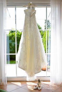 pretty wedding dress from behind hanging on a window with bridal shoes by © radmila kerl photography munich schönes Bild von einem Brautkleid von hinten mit den passenden Brautschuhen