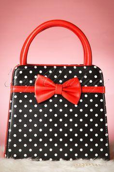 Die50s Carla Polkadot Handbagist ein echter Blickfang mit der wuderschönen Farbe, den süßen Polkadots und den eleganten Schleifchen!Wie süß! Hergestellt aus Kunstleder in Schwarz und Rot mit süßen weißen Polkadots und eleganten Schleifchen auf der Vorder- und Rückseite. Die Tasche hat robuste Henkel, wird mit einem Reißverschluss verschlossen, ist vollständig in Schwarz mit cremefarbenen Polkadots gefüttert und...